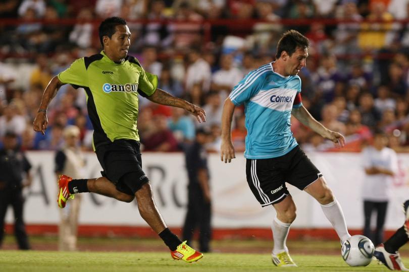 Restrepo persigue a Messi durante un juego de exhibición en Cancún.