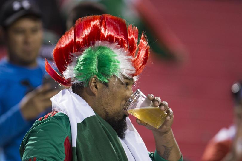 Un aficionado disfruta de su cerveza durante un partido del Tri