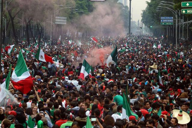 Aficionados mexicanos festejan a la Selección Mexicana en el Ángel de la Independencia.