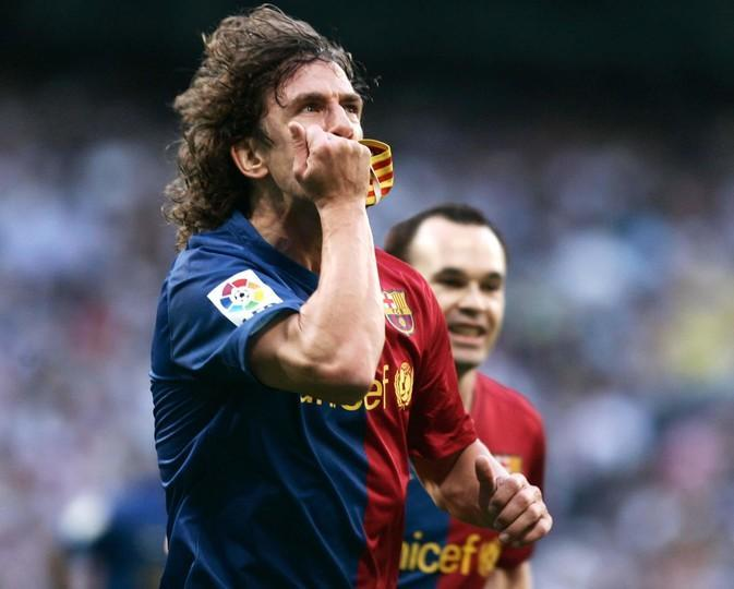 Puyol besando el gafete de capitan con la bandera de Cataluña.