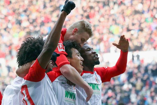 Jugadores del Augsburg celebran el primer gol del partido