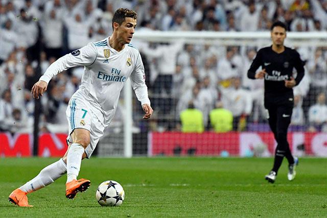Cristiano conduce el balón mientras Neymar lo observa