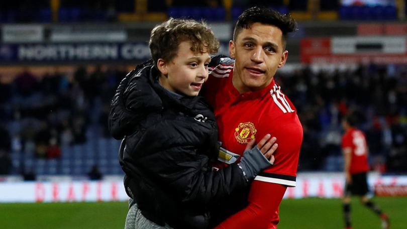 Alexis Sánchez abrazando a un pequeño