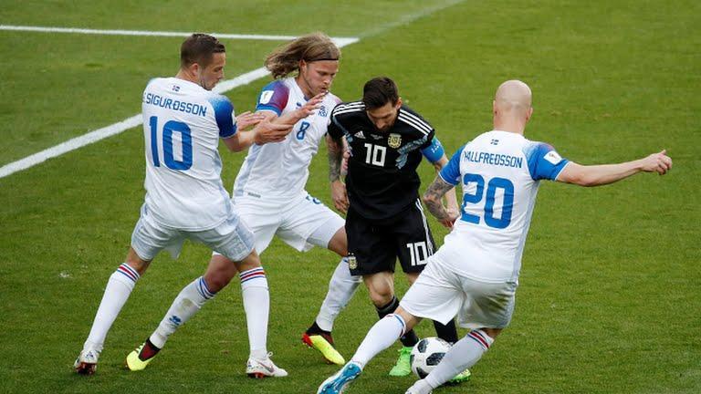 Messi entre tres jugadores de Islandia