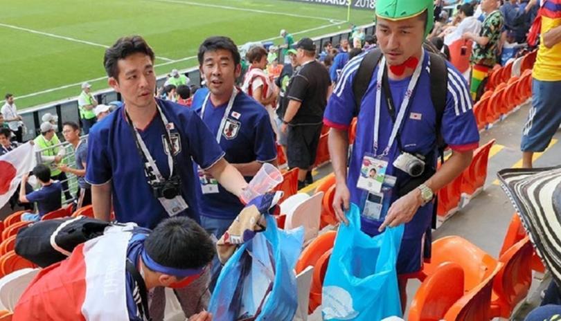 Aficionados de Japón limpian el estadio.
