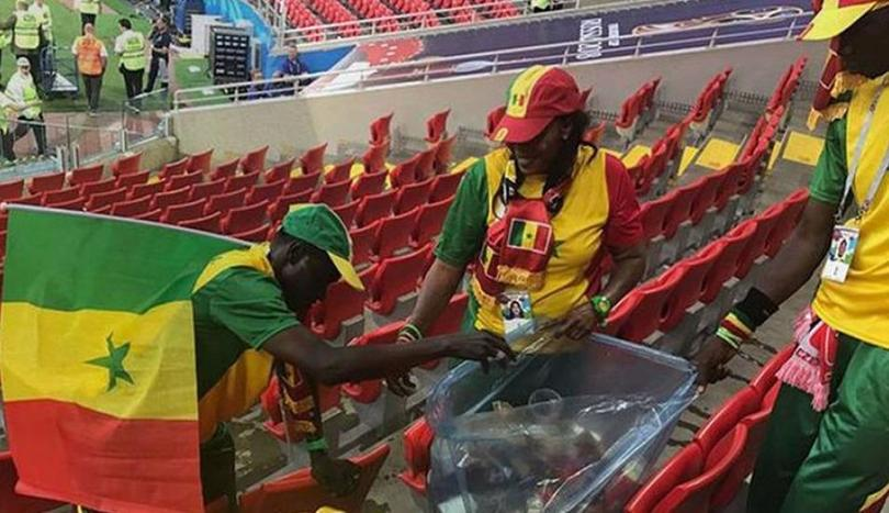 Aficionados de Senegal limpiando el estadio