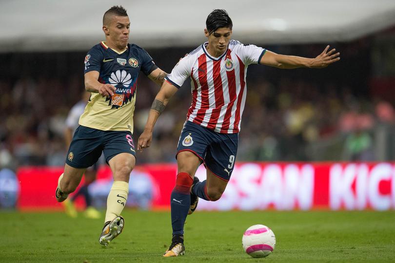 Mateus Uribe disputando un balón contra Alan Pulido