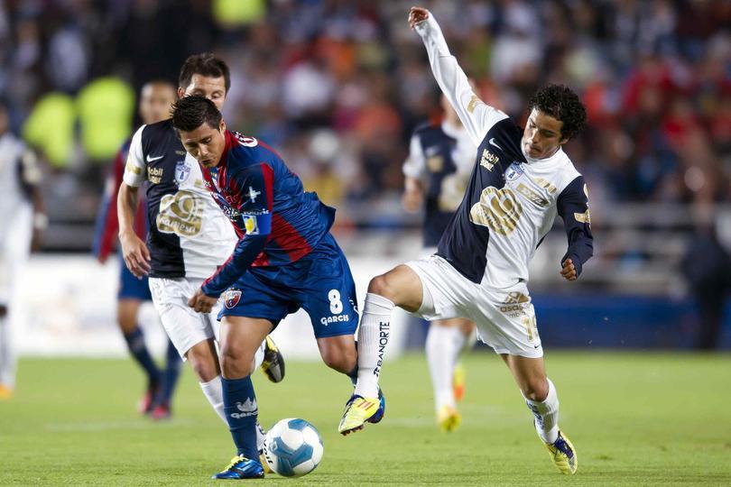 Osvaldo Martínez disputando un balón en un Atlante contra Pachuca