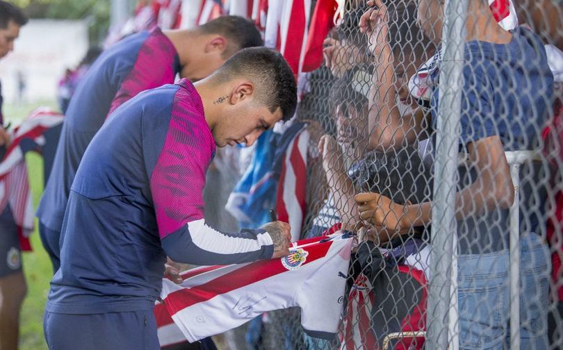 Víctor Guzmán firmando la playera de un aficionado