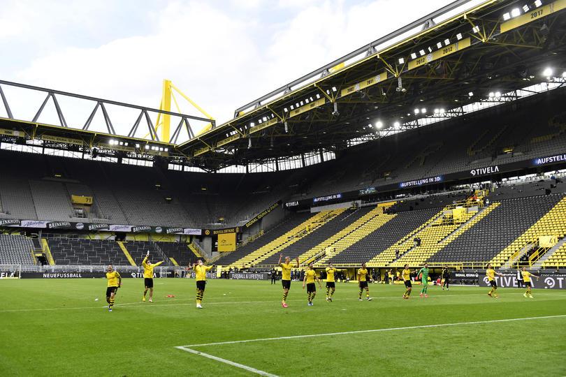 Jugadores celebran hacia la tribuna del estadio, como si estuviera llena