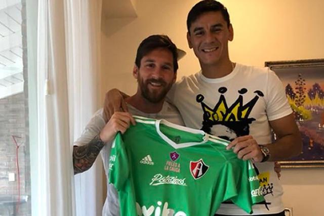 Lionel Messi y Óscar Ustari posando con el jersey del Atlas